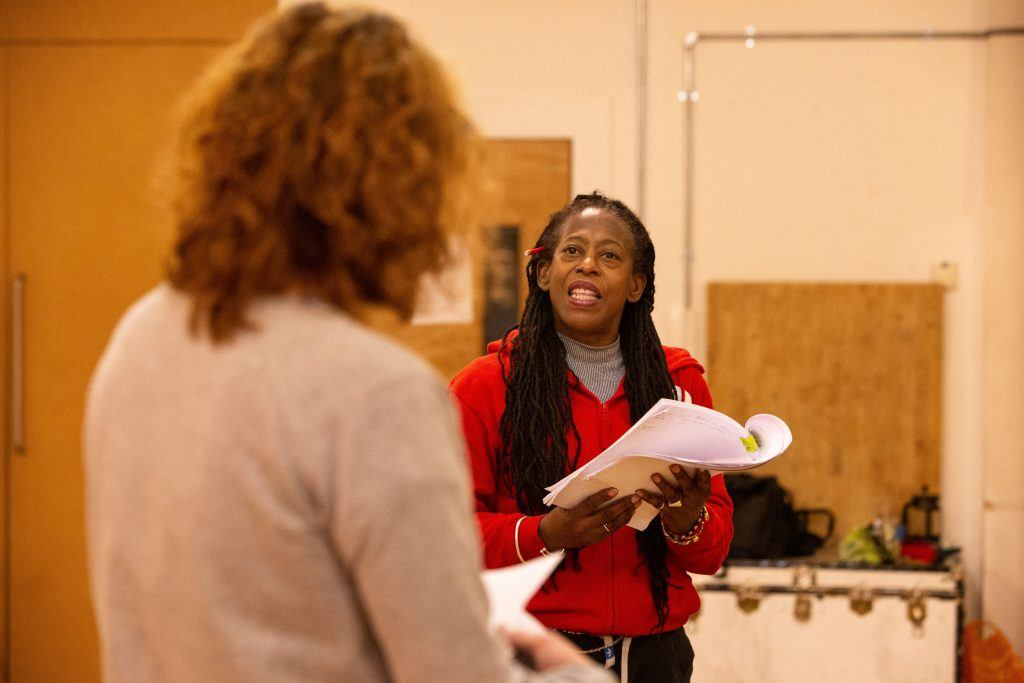 Two actors reading from scripts in a rehearsal room