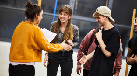 Three young people stand laughing in a group in a rehearsal