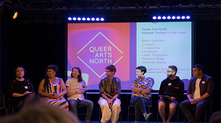 A panel are answering questions from the audience , seated in front of a screen displaying Queer Arts North in neon light.