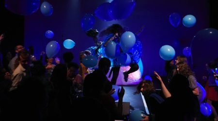 A group of people standing and enjoying a performance as blue balloons fall from above.